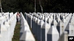 A Bosnian Muslim woman reacts as she walks among gravestones at the memorial centre of Potocari near Srebrenica, 150 kms north east of Sarajevo, Bosnia, Aug. 14, 2018.