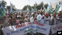 Supporters of the religious and political party Jamaat-e-Islami hold a banner that reads 'Pakistani Demand to Hang Raymond Davis Immediately' while praying during a protest rally in Karachi, January 30, 2011.