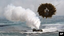 FILE - The 2015 Livelihood Award honors the Marshall Islands prime minister and people for suing nuclear powers over their failure to disarm. Shown here is a South Korean marine LVT-7 landing craft sailing through a smoke screen during joint U.S.-South Ko
