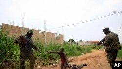 Les soldats des Forces républicaines capturent deux miliciens présumés dans le quartier Riviera I à Abidjan, Côte-d'Ivoire, 13 avril 2011. (AP Photo / Rebecca Blackwell)
