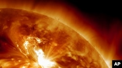 This handout image provided by NASA, taken Sunday night, Jan. 22, 2012, shows a solar flare erupting on the Sun's northeastern hemisphere.