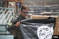 An Iraq soldier poses with an upside-down captured Islamic State flag, July 2, 2017 in Mosul, Iraq. Soldiers say despite their imminent victory in Mosul, the battle with IS is far from over. (H. Murdock/VOA)