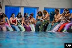 Mermaids dan Mermen berkumpul di sekitar kolam renang utama untuk foto bersama saat berlangsungnya MerMagic Con di Freedom Aquatic Center, Manassas, Virginia, 7 Agustus 2021. (AFP)