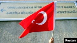 FILE - A person holds a Turkish flag under a sign on the U.S. Consulate in Istanbul.