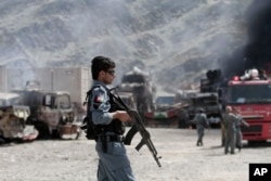 FILE - An Afghan policeman stands guard near burning NATO supply trucks following an attack by militants in the Torkham area near the Pakistan-Afghanistan border in Jalalabad province east of Kabul, Afghanistan, Sept. 2, 2013.