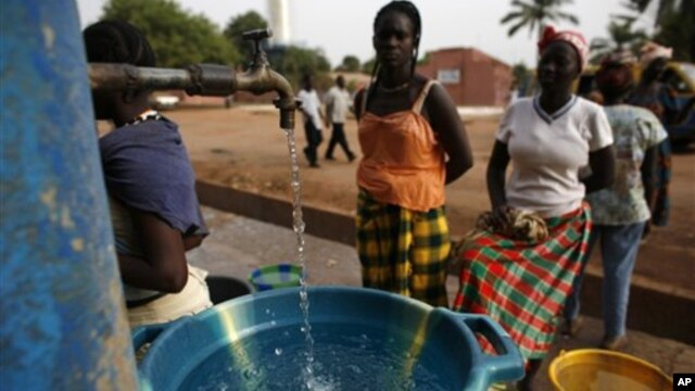 Girls fill plastic basins at a free water tap in a neighborhood where houses with indoor plumbing rarely receive water, in Bissau, Guinea-Bissau, March 6, 2009. Contaminated drinking water leads to yearly cholera epidemics, particularly in remote rural re