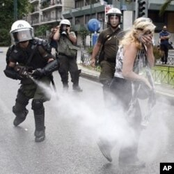 A policeman sprays tear gas as a protester walks away during an anti-austerity rally in Athens June 29, 2011.