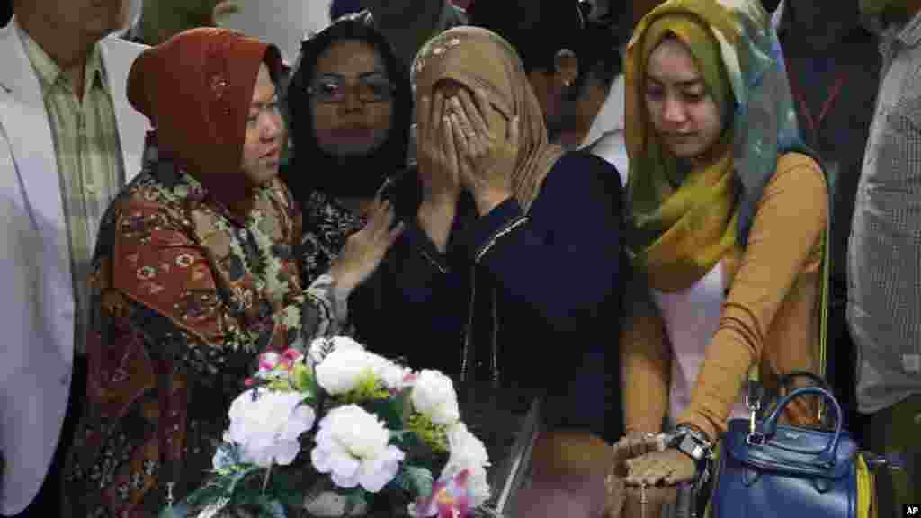 A relative weeps during the handover of the body of Hayati Lutfiah Hamid, one of the victims of AirAsia Flight 8501, to her family at the police hospital in Surabaya, East Java, Indonesia, Jan. 1, 2015.
