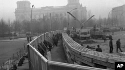 This Nov. 20, 1961 photo shows 12 feet high boards hiding the work as East German troops erect a new concrete wall at the Brandenburg Gate, marking the East-West border in Berlin. In background is the former Reichstag building which is in West Berlin. (A