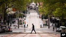 People cross Bourke Street in Melbourne, Australia, Sept. 30, 2021.