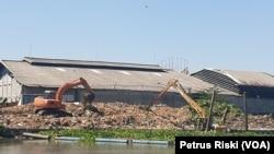 Dua eskavator memindahkan tumpukan sampah yang ada di pinggir sungai Surabaya wilayah Gunungsari, Surabaya, setelah terjaring pipa yang dipasang melintang di atas sungai (Foto: VOA/Petrus Riski)