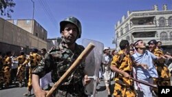 Yemeni riot police charge towards anti-government protesters, during a demonstration demanding the resignation of President Ali Abdullah Saleh, in Sana'a, February 18, 2011