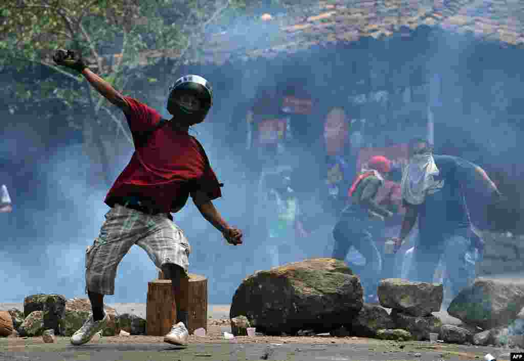 Residents of El Hatillo throw stones at riot police during a protest against the construction of a housing project in the outskirts of Tegucigalpa, Honduras, Sept. 17, 2019.