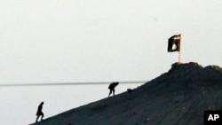 Chiến binh Nhà nước Hồi giáo đặt cờ trên một đỉnh đồi ở phía đông của thị trấn Kobani, Syria.