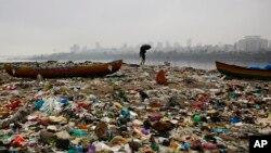 Seorang nelayan India berjalan di pantai Laut Arabia yang penuh dengan sampah di Mumbai (foto: dok). Pemerintah India hari Minggu (2/10) meratifikasi perjanjian iklim yang disepakati di Paris.