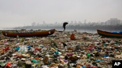 A fisherman walks on the shores of the Arabian Sea, littered with plastic bags and other garbage, in Mumbai, India.