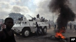 UN peacekeepers drive past supporters of Alassane Ouattara as they demonstrate and burn tires in the Abobo neighbourhood in Abidjan.
