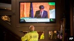 Orang-orang di bar menyaksikan pidato Pemimpin Catalan Carles Puigdemont lewat layar lebar di Barcelona, Spanyol (10/26).
