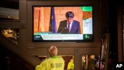 People in a bar watch the speech of Catalan regional president Carles Puigdemont on television in Barcelona, Spain, Oct. 26, 2017.