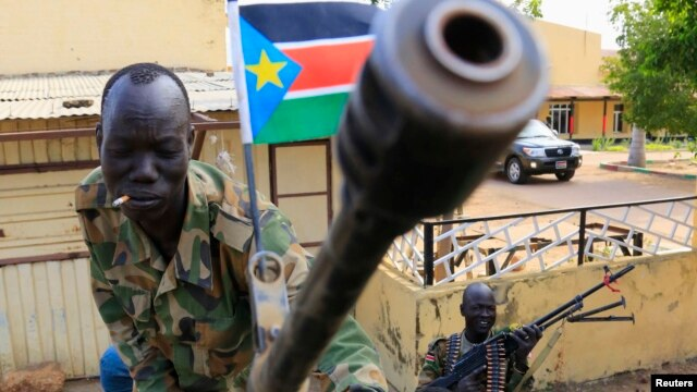 A South Sudan army soldier stands next to a machine gun mounted on a truck in Malakal, capital of Upper Nile state, which an official says is controlled by forces loyal to former Vice President Riek Machar.