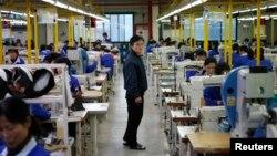 지난해 12월 개성공단 내 남측 입주기업에서 북한 노동자들이 작업 중인 가운데, 북한 관리 인력(가운데)이 이를 감독하고 있다.