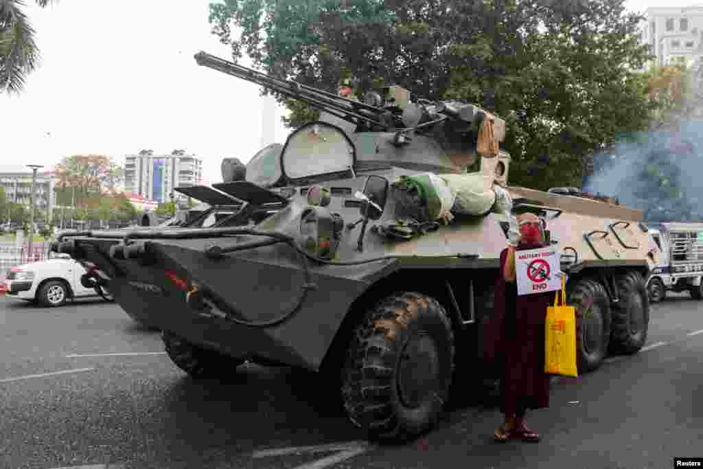 A Buddhist monk holding a sign stands next to an armored vehicle during a protest against the military coup, in Yangon, Myanmar.