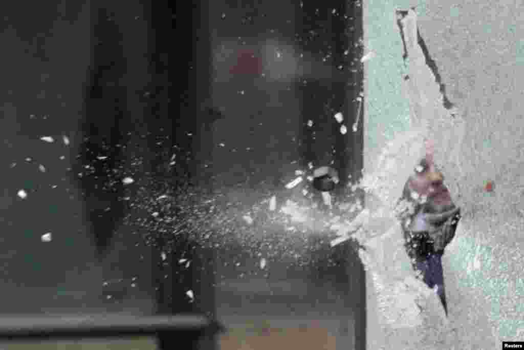 Un perno lanzado por un empleado de la firma acerera Arcelor Mittal rompe el vidrio de una parada de bus en Estrasburgo, Francia, durante una protesta contra el cierre de puestos de trabajo.