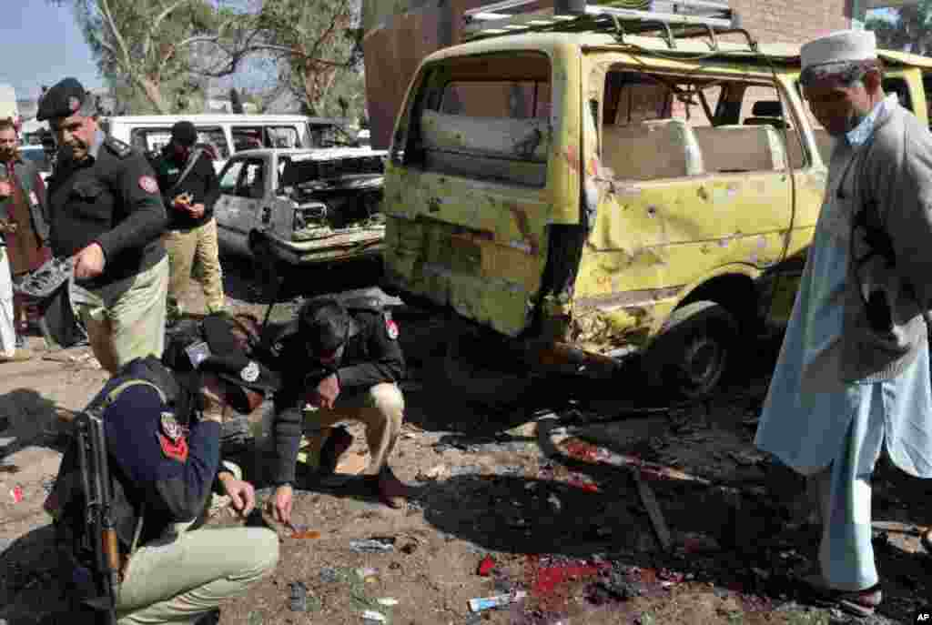 Pakistani policemen inspect the site of a car blast on the outskirts of Peshawar on February 23, 2012. (AFP Photo)