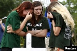 Mourners gather at a makeshift memorial left in memory of the victims killed in a shooting at Santa Fe High School in Santa Fe, Texas, May 21, 2018.