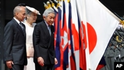 Cambodian King Norodom Sihamoni, left, follows Japanese Emperor Akihito, right, and Empress Michiko, center, on their way to a welcoming ceremony at the Imperial Palace, in Tokyo, Japan, Monday, May 17, 2010.