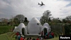 Anak-anak di sekolah pendidikan dini Hounslow Heath di London mengelilingi salah satu dari empat bangunan berkubah di sekolah mereka yang dibangun untuk meredam suara pesawat. (Reuters/Stefan Wermuth)