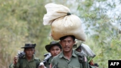 Binh sĩ mang gạo đến khu vực xảy ra động đất ở Tarlay, 28/3/2011