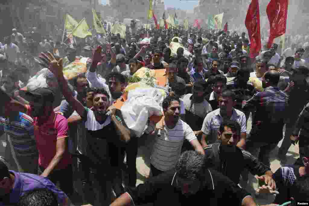 Palestinians carry the bodies of members of the Kaware family that hospital officials said were killed in an Israeli air strike on their house, during their funeral in Khan Younis in the southern Gaza Strip, July 9, 2014.