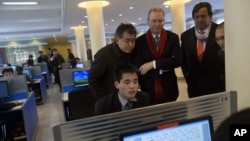 Executive Chairman of Google, Eric Schmidt (C) and former New Mexico governor Bill Richardson (2nd R) watch as a North Korean student surfs the Internet at a computer lab during a tour of Kim Il Sung University in Pyongyang, January 8, 2013.