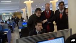 Tổng giám đốc Google Eric Schmidt (giữa), và cựuThống đốc New Mexico Bill Richardson (thứ 2, phải) xem một sinh viên Bắc Triều Tiên sử dụng internet tại phòng thực nghiệm trong khi 2 ông đến thăm Đại học Kim Il Sung ở Bình Nhưỡng, 8/1/13