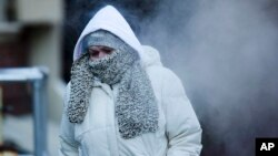 A commuter walks along Market Street in freezing temperatures Tuesday, Nov. 18, 2014, in Philadelphia, Pennsylvania.