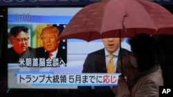 "FILE - A woman walks past a public TV screen showing North Korean leader Kim Jong Un, left, and U.S. President Donald Trump, right, in Tokyo, March 9, 2018. The signs reads: ""Trump has accepted an offer of a summit from the North Korean leader and will meet with Kim by May."""