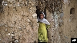 FILE - An Afghan refugee girl outside her home in slums of Islamabad, Pakistan.