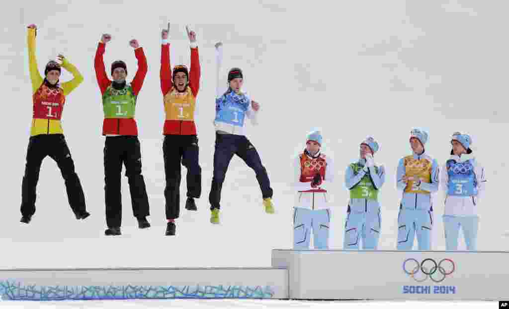 Germany's team Eric Frenzel, Bjoern Kircheisen, Johannes Rydzek and Fabian Riessle, from left, celebrate winning the silver as Norway's gold medal winners Magnus Hovdal Moan, Haavard Klemetsen, Magnus Krog and Joergen Graabak, from left, applaud during the flower ceremony of the Nordic Combined Gundersen large hill team comptetition, Sochi, Feb. 20, 2014. during the flower ceremony of the Nordic combined Gundersen large hill team competition at the 2014 Winter Olympics, Thursday, Feb. 20, 2014