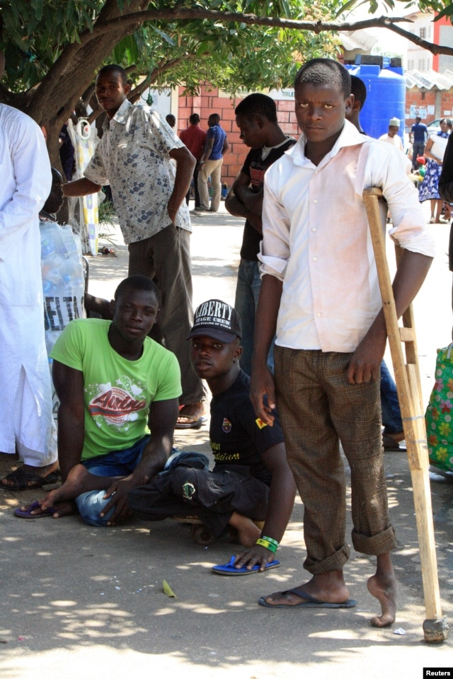 These young men say that polio not only robbed them of the use of their legs, but of their ability to work for a living. They say they beg for money in this Abuja market for food and school fees. (VOA/H. Murdock)