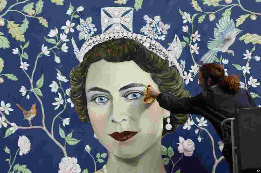 Một nhân viên gắn một bức bích họa mới hình Nữ hoàng Anh Elizabeth II của họa sĩ Frederick Wimsett để mừng sinh nhật lần thứ 90 của bà ở trung tâm London. Nữ hoàng Elizabeth II, người trị vì lâu nhất trong lịch sử nước Anh, sẽ tròn 90 tuổi vào ngày thứ Năm này.