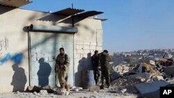 ພວກນັກຮົບຊາວ ເຄີດ ຢືນເບິ່ງປະຊາຊົນ ຫຼົບໜີອອກຈາກ ໝູ່ບ້ານທີ່ຖືກພວກກະບົດຄວບຄຸມໃນພາກຕາເວັນອອກຂອງ ເມືອງ Aleppo ເຂົ້າໄປໃນຂົງເຂດ Sheikh Maqsoud ທີ່ຖືກຄວບຄຸມໂດຍພວກນັກຮົບຊາວ ເຄີດ, 27 ພະຈິກ, 2016.
