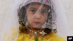 FILE - Three-year-old Sunam is dressed in a bridal outfit in Kabul, Afghanistan, Aug. 14, 2007.