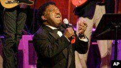 "FILE - Percy Sledge kneels as he performs ""When a Man Loves a Woman"" along with the Muscle Shoals Rhythm Section at the Musicians Hall of Fame awards show in Nashville, Tennessee, Oct. 28, 2008."
