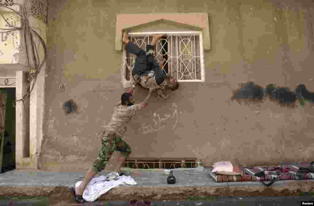 A member of the Free Syrian Army pretends to fall out of a window as he jokes around with a colleague in Deir al-Zor, Syria.
