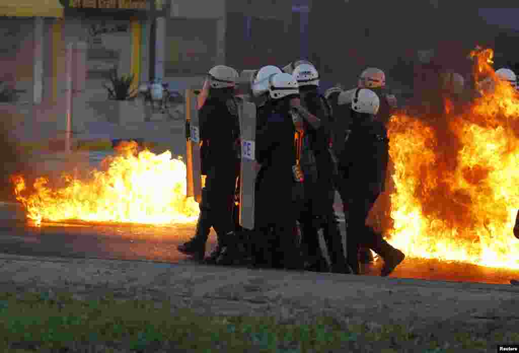 Riot police advance behind the cover of their shields as flames from Molotov cocktails thrown by anti-government protesters burn around them during clashes in Budaiya, west of Manama, Bahrain.