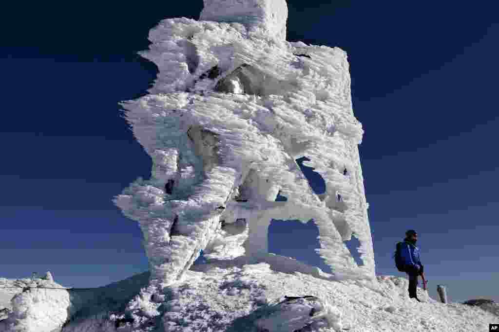 បុរសម្នាក់ឈរនៅជិតអង់ទែនគ្របដណ្តប់ដោយទឹកកកមួយនៅអំឡុងពេលកិច្ចប្រជុំកំពូលមួយនៅក្រុង Mount Washington រដ្ឋ New Hampshire កាលពីថ្ងៃទី២៣ ខែកុម្ភៈ ឆ្នាំ២០២០។