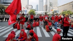 Para pekerja beristirahat di sela pawai Hari Buruh (May Day) di Jakarta, Indonesia, 1 Mei 2018. (Foto: REUTERS/Beawiharta)