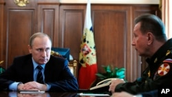 FILE - Russian President Vladimir Putin, left, and General Viktor Zolotov, commander of Interior Ministry troops, confer in the Kremlin in Moscow, April 5, 2016. Zolotov is slated to lead the new National Guard.