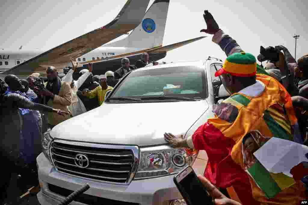 La foule salue l'ancien président Amadou Toumani Touré venant de débarquer d'un avion à Bamako, le 24 décembre 2017.